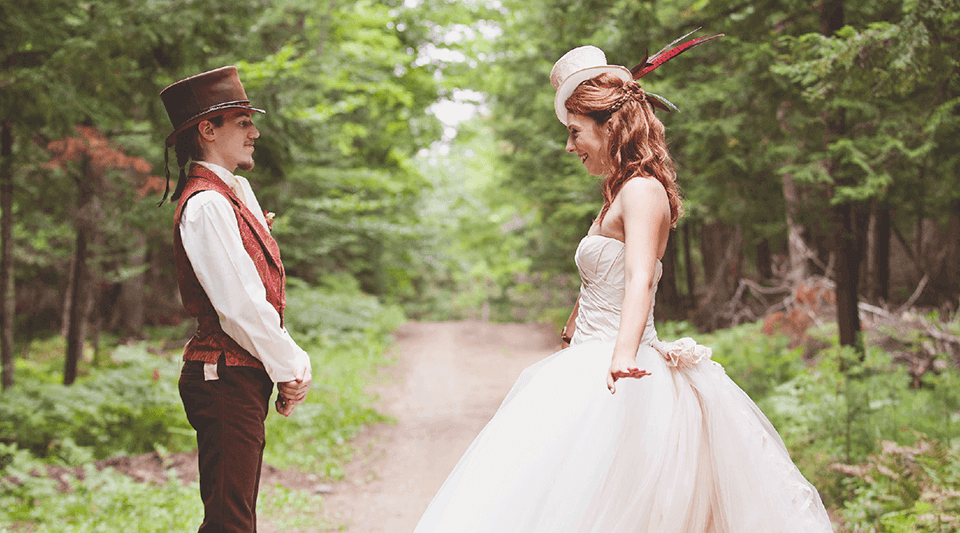 Erty and Greta standing in the forest in their wedding outfits.